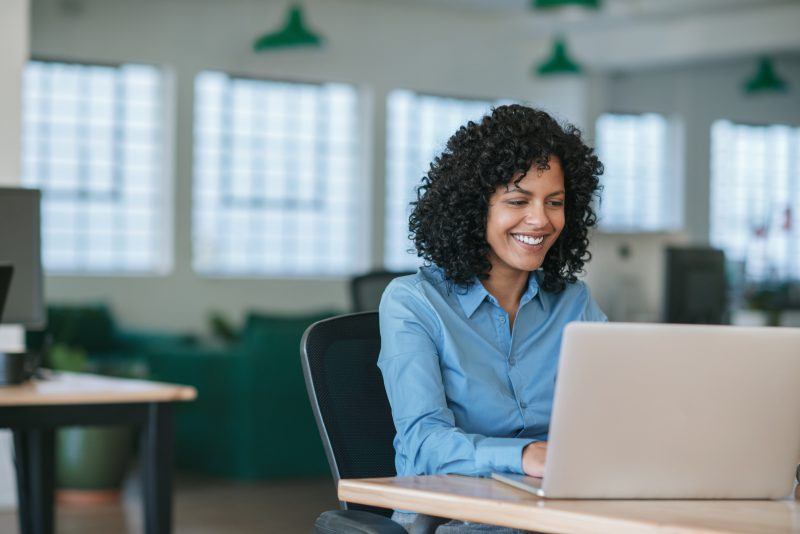 Smiling young businesswoman sitting at her desk in a large modern office working online with a laptop