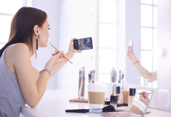 Beauty blogger filming makeup tutorial with smartphone in front of mirror .