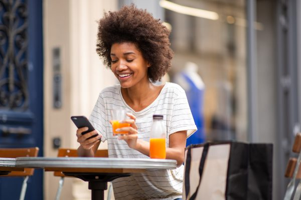 Portrait of beautiful young black woman sitting at outdoor cafe with cellphone and drink
