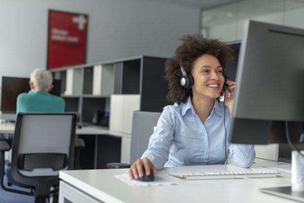 Photo of smiling, Cheerful mixed-race girl call working in center operator, wearing business attire. Young Customer service executive woman working at office. Female Customer service executive talking on headset in office. Young attractive friendly customer service answering customer questions on the telephone with toothy smile.