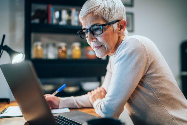 Senior woman working at home using lap top