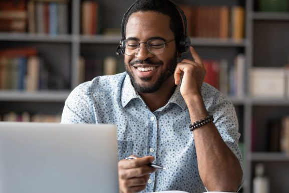 Smiling African American man in glasses and headset watch webinar on laptop making notes, happy biracial male student worker in headphones handwriting studying or working using computer